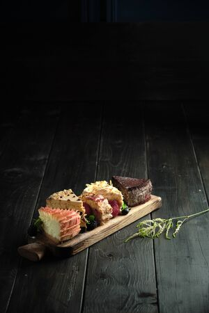 Different pieces of cakes on a wooden board . catering menu Stockfoto