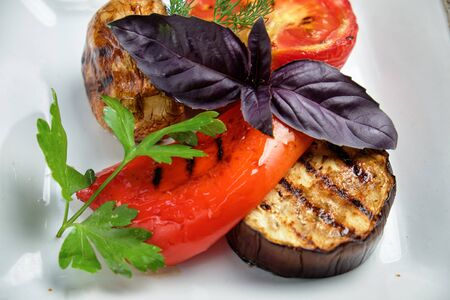 Grilled vegetables on a white plate on a dark wooden background. catering menu Stock Photo