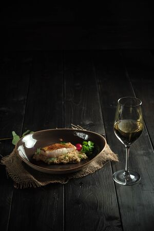 Meat steak with pearl barley on a brown plate and a glass of white wine on a dark wooden background. catering menu