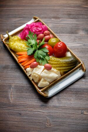Pickled vegetables on a white rectangular plate on a brown wooden background. Menu