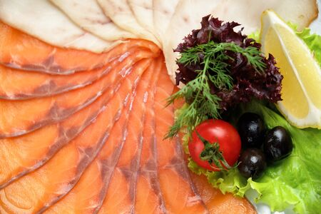 White and red fish sliced in thin slices on a white round plate in a beautiful serving on a brown rustic background. restaurant menu Standard-Bild