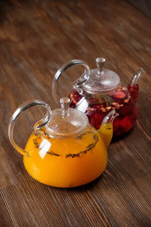 Hibiscus tea and sea buckthorn tea in a transparent teapot on a dark wooden background. catering menu 写真素材