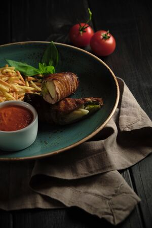 Meatloaf with potatoes straws with sauce on a blue plate on a dark wooden background. catering menu