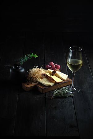 Glass of cold white wine with cheese snack on a wooden board on a dark wooden background. catering menu