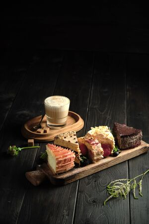 Different pieces of cakes on a wooden board and a glass of cappuccino on a dark wooden background. catering menu