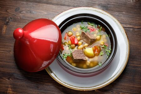 Beef soup in a pot with a red lid on a dark wooden background. Restaurant menu