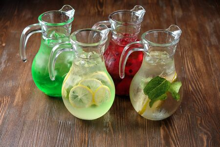 Different soft drinks in transparent jugs on a dark wooden background. menu for catering Stockfoto