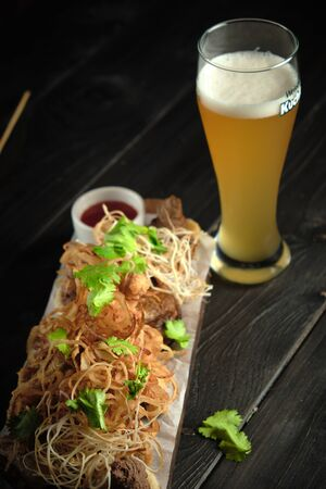 Glass of cold beer with appetizer on wooden boards on a dark wooden background. catering menu