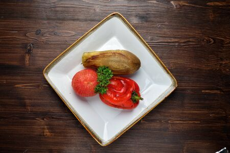 Grilled vegetables on a white plate on a dark wooden background. catering menu 写真素材