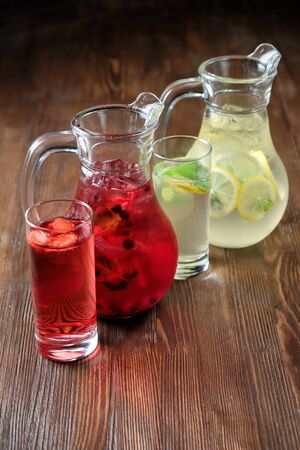 Different soft drinks in transparent jugs on a dark wooden background. menu for catering Standard-Bild