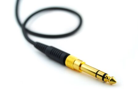 Golden headphone plug with wire isolated on white background with place for text (low depth of field) photo