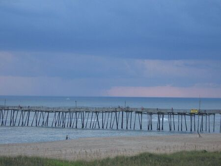 storm coming: Storm coming in over the ocean fisherman and pier in forground Stock Photo