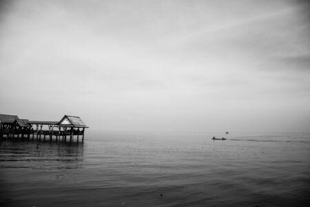 Serene calm sea and peer. black and white image