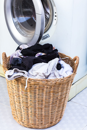 Dirty clothes in basket and washing machine
