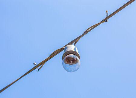 Old light decor bulb on blue sky Imagens