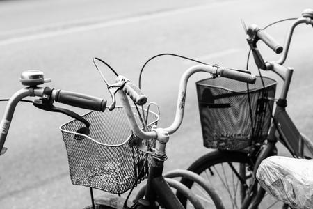 Blak and white photo of bicycles in city