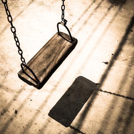 Empty wooden swing in retro filter