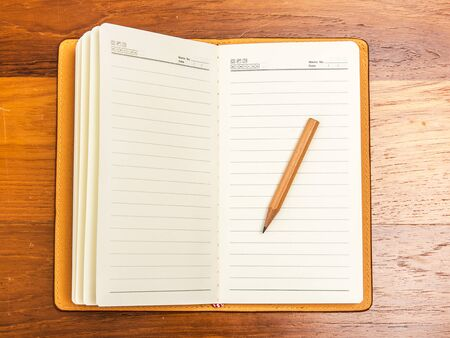 Top view blank note book with pencil on wooden table