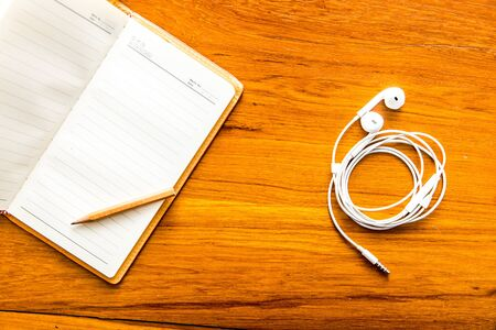 Top view open notebook with earphone on office table