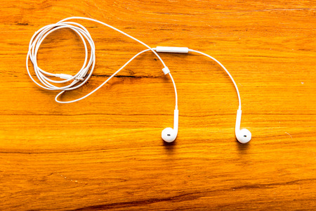 Modern EarPods on wood background Stock Photo