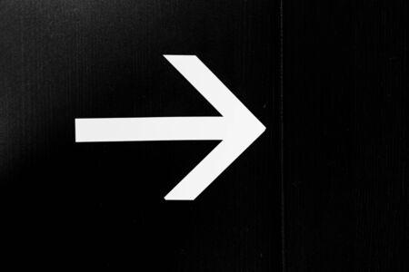 Arrow direction sign on black Imagens