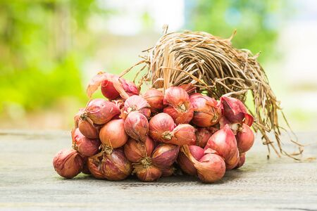 Red onions on wooden table