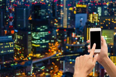 Hand hold blank smartphone on blue city light background Imagens