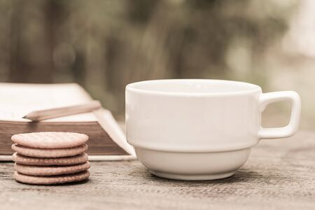 Retro hot coffee on table with cookies and old book in garden Imagens