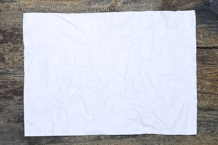 Blank wrinkled paper on woodenbackground
