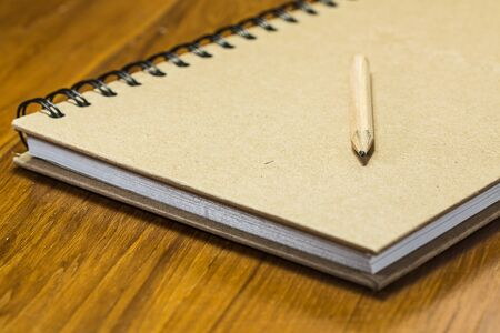 Note book and pencil on wooden table