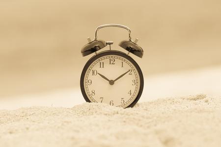 Reloj despertador vintage en la playa de arena Foto de archivo