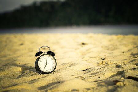 Alarm clock on tropical sand beach