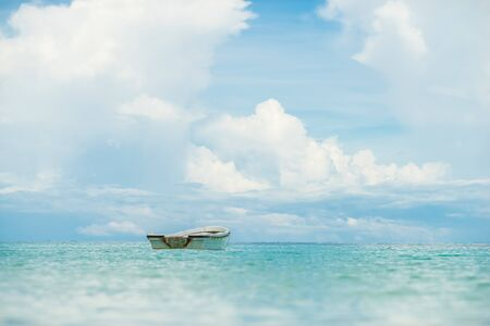 Lonely small boat in blue ocean