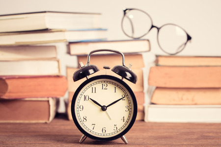 education concept. alarm clock on stacked old book backcground Stock Photo