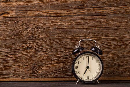 Vintage alarm clock on grunge wood background