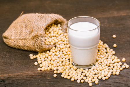 Soy milk and beans on wooden table Foto de archivo - 122679134