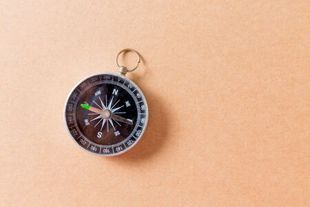 Compass on brown paper background