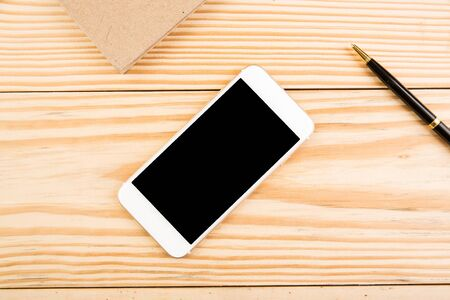 Top view blank smartphone on wooden background Imagens