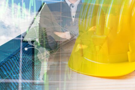 Double exposure safety helmet on trading graph and building background