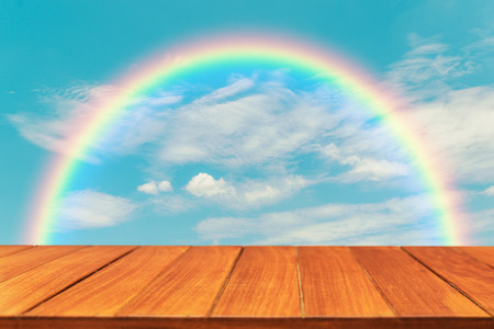 wood table top on rainbow sky background