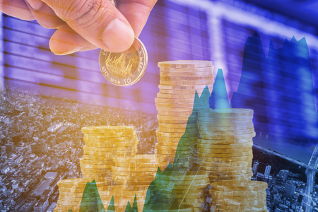 Double exposure hand punt money coins on business reading graph and stock board