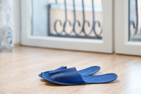 Ragged blue sneakers on the laminate floor. Stock Photo