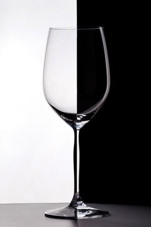 Wineglass on the border of black and white backgrounds.