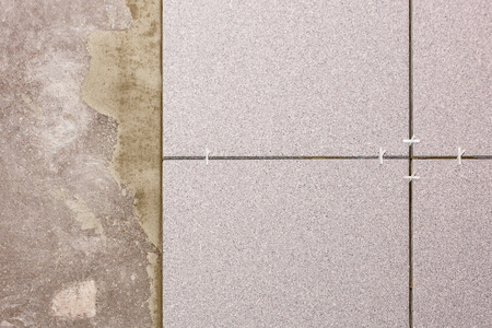 Fragment of the floor, in the process of laying ceramic tiles, close-up. Standard-Bild