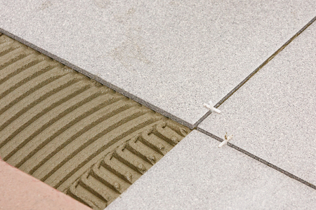 Fragment of the floor, in the process of laying ceramic tiles, close-up. Stockfoto