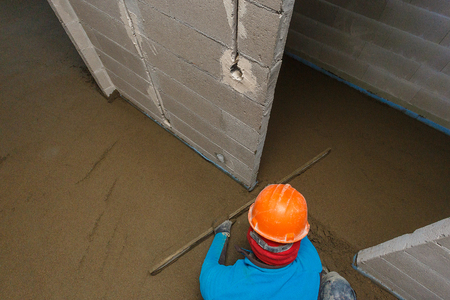 The laborer in an orange helmet is leveling the floor screed solution. Stock Photo