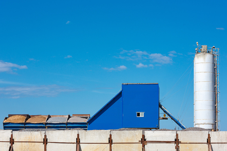 Components for the production of cement in containers against the blue sky.