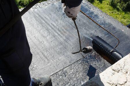 Pose d'étanchéité sur le sol du balcon, lors de la construction d'un immeuble à appartements.