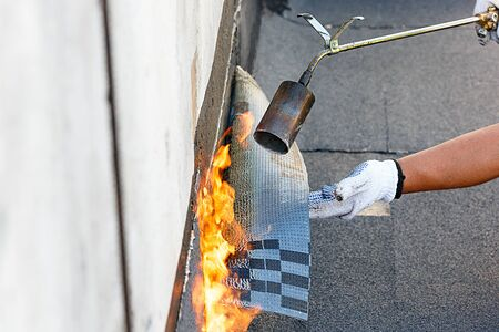 Laying waterproofing by heating roofing felt with fire.