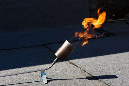 Układanie hydroizolacji poprzez ogrzewanie papy dachowej ogniem.